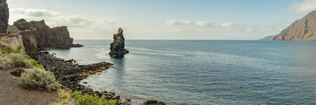 Wide angle panorama. Roque de Bonanza is one of the symbols of El Hierro island and its natives. Huge Rock sticking out of the water on the las Almorranas beach. El Hierro, Canary islands Spain. 版權商用圖片