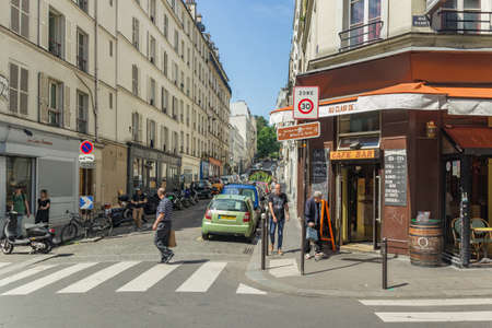 Paris, France - June 23, 2016: Quiet and cozy street of Paris near Montmartre. Nearly parked cars and motorbikes along narrow paving stones and locals on the sidewalk. Editorial