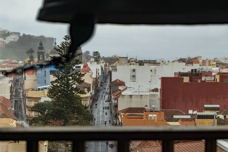 Top view through the slatted window from the high tower of the church. Outside the window are low gray clouds and drizzling rain. Silhouette of a church bell in a window. La Laguna, Tenerife.