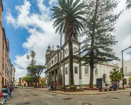 SAN CRISTOBAL DE LA LAGUNA, SPAIN - JUNE 16, 2015: Cathedral of San Cristobal de la Laguna. Old Dragon trees in front of main entrance. Tourists and locals walk along the numerous pedestrian streets.