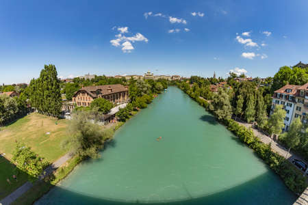 Bern, Switzerland - July 30, 2019: Aerial view of Aar from the Monbijoubrucke Bridge. Brige over the Aare river. Bern Switzerland. The Parliament Building on the background. Super wide angle panorama.