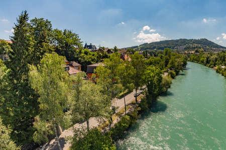 Bern, Switzerland - July 30, 2019: Aerial view of Aar from the Monbijoubrucke Bridge. Brige over the Aare river. Gurten Park on the green hill on the background. Bern Switzerland