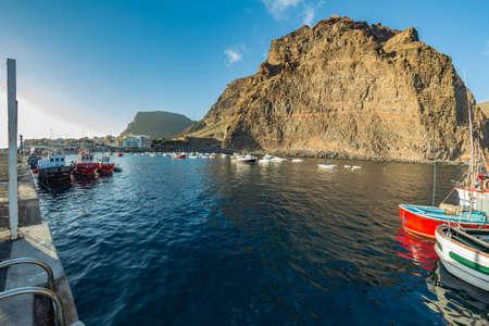 Playa De Vueltas beach and Port with yacht and fishing boats at the atlantic ocean in La Gomera. A popular vacation spot for tourists and locals. Valle Gran Rey, Canary islands, Spain.