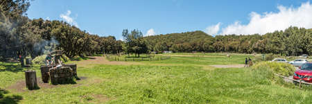 Super wide panorama of Picnic barbecua area in the center of the unique relict forest of National Park surrounded by young green grass. Laguna Grande, La Gomera, Canary Islands