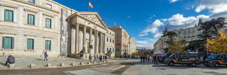 MADRID, SPAIN - DECEMBER 13, 2018: Congreso De Los Diputados in the Palace of the Parliament, or Plaza de las Cortes. Police cars parked in front of the Main entrance. Super wide angle panorama.