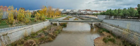 MADRID, SPAIN - DECEMBER 13, 2018: The Arganzuela bridge over Manzanares River downtown Madrid, Spain. It is a futuristic structure built in 2011. Super wide angle panorama.