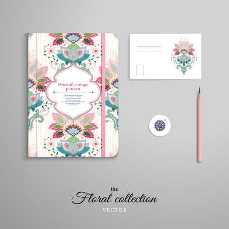Set of notebook, pencil, tag and card. Figured frame. Floral pattern of indian flowers. Wooden texture on backdrop.