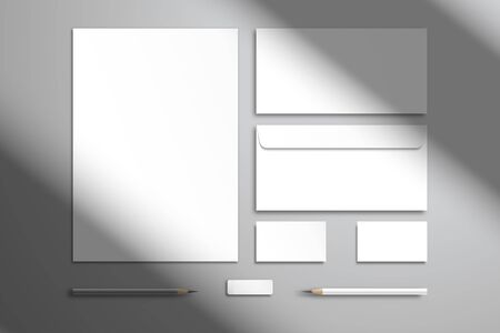 Flat layout with branding kit. White sheet of paper, two envelopes, two business cards, pencils and an eraser. Realistic template for design with shadow from the window