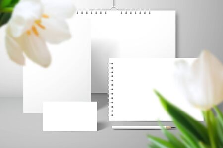 Stationery set for branding and large tulip flowers in the foreground. Calendar, album, notebook, business card and pencil. Mockup for design with a shadows