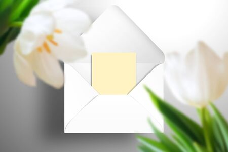 A white open envelope and a yellow blank greeting card in it. In the foreground, large tulip flowers in defocus. Realistic template for design Illustration