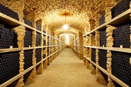 Old cellar of the wineryBottles of wine in the futureHuge warehouse wine Foto de archivo