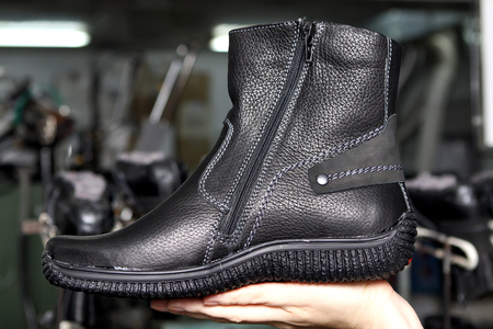 Production designer shoes. Footwear production by human hands. Shoe factory.