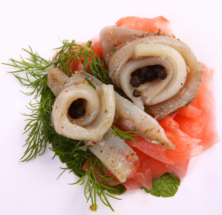 Herring on a red pepper. Herring fillet on sweet peppers. Capelin fillets in an exclusive dish. Fish fillet. Exclusive dish of fish.