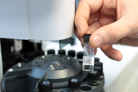 chromatograph: Scientist holds a chemical sample bottle. Doctor hand in medical glove with clinical chemistry samples putting them to centrifuge. People hand holding a test tube vial sets for analysis in the gas liquid chromatograph. Laboratory assistant inserting labor