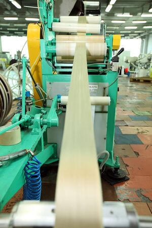 Manufacture of a natural shell for sausage. Collagen shell for sausages. Collagen casings industry for sausage products. Film for sausages. Large scale production. Stock Photo - 134377145