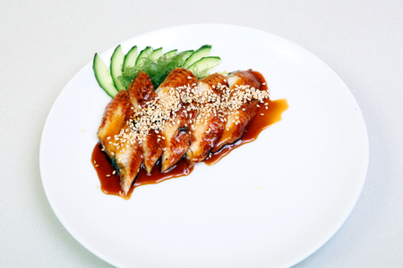 Smoked eel with gravy and cucumber. Sashimi Unagi. Japanese food on a beautiful dish. Dietary food. An exquisite Japanese dish. Dietary.