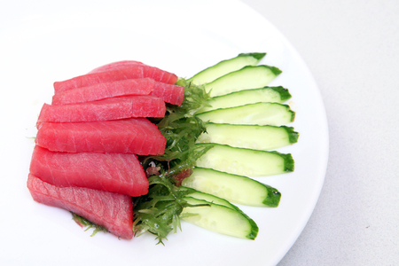 Sashimi.Tunse sliced with seaweed and cucumber. Japanese food on a beautiful dish. Dietary food. An exquisite Japanese dish.