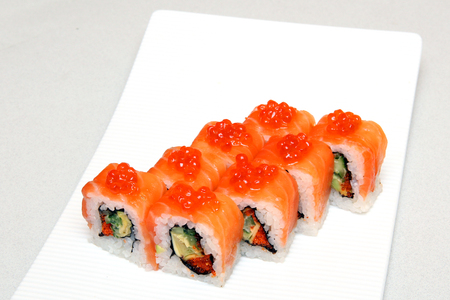 Roll with caviar of salmon. Sushi with caviar of flying fish. Japanese food on a beautiful dish. Diet food. Imagens