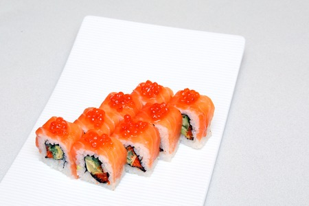 Roll with caviar of salmon. Sushi with caviar of flying fish. Japanese food on a beautiful dish. Diet food. Reklamní fotografie