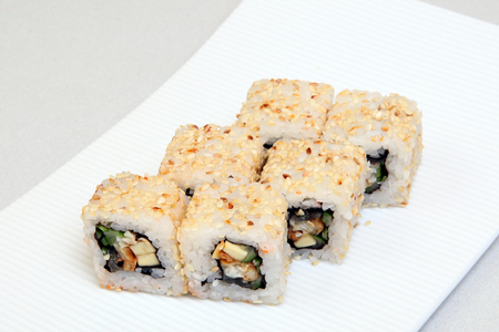 Roll California in sesame. Sushi with crab, eel, cucumber. Japanese food on a beautiful dish. Diet food.