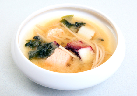 Japanese soup with red fish. Soup with soy cheese Tasty healthy food. Dietary soup with mushrooms. Soup in a bowl.