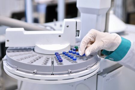 Quality Control Laboratory medicine. Chromatograph operation. A woman makes an analysis on a gas chromatograph. Development of a new vaccine against the covid-19 virus.Pharmaceutical factory
