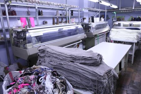 Pink spools of thread on the background of the sewing workshop. Clothing industry. Machine for the textile industry. Manufacture of wearing apparel. New factory for tailoring