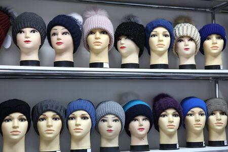 Mannequin heads in knitted hats and scarves. Mannequins female heads in hats and scarfs close up. Woolen knitted caps and scarves. Female headdresses.