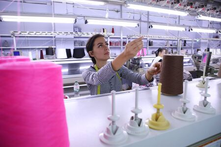 Girl on the background of sewing production. Beautiful girl is programming a machine for sewing designer clothes. Pink spools of thread on the background of the sewing.