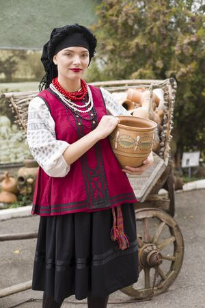 Beautiful girl in national dress. Holding an ancient pot in his hands. Antique clothing of the late 19th century. Beautiful dress and skirt on a woman. The concept of rural life, national traditions Stock Photo