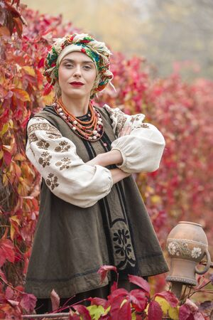 Beautiful girl in national dress. With an ancient clay pot. Antique clothing of the late 19th century. Beautiful dress and skirt on a woman. Beautiful autumn and leaves. Clothing of the late 19th century.
