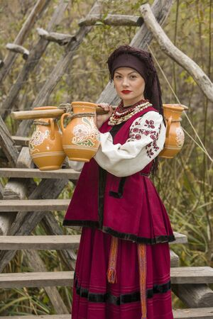A woman in traditional clothes carries water in old barrels. Old jugs are carried by a girl in a stylized suit. Beautiful, original clothes of the 19th century. Against the background of the bridge