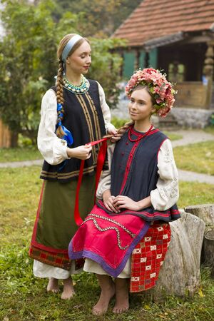 Two beautiful girls in national clothes of the late 19th century. A woman weaves ribbons in her daughters hair. Old clothes. Retro staging of an ancient rite. Beautiful dress and skirt on a woman. Old housing on the background