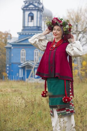 Girl and guy in retro costumes on the street in the old village. Retro staging of an ancient rite. Beautiful wreath on a girl. The guy hugs the girl, both are smiling. Antique clothing of the late 19th century