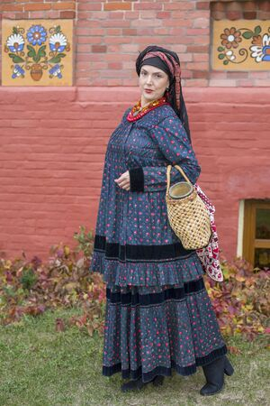 Woman with a basket in retro clothes of the 19th century. Antique clothing of the late 19th century. Beautiful dress and skirt on a woman. Beads and decoration on a girl. Ancient place. Tradition and culture of the old world