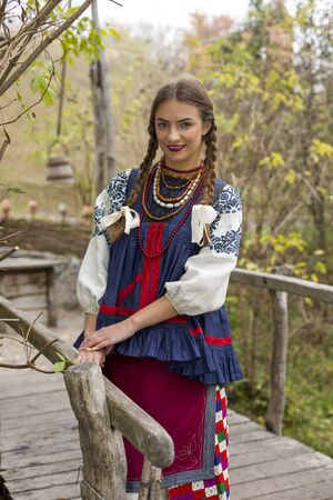 A girl in national dress is walking through an old bridge. Old clothes. Retro staging of an ancient rite. Beautiful dress and skirt on a woman. Beads and decoration on a girl. Retro clothes of the 19th century. Ancient place Stock Photo