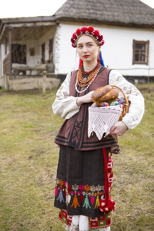 Beautiful girl in national dress with Easter and eggs in a basket. Easter holiday. In old clothes of the 19th century. With a wreath and ribbons. Against the background of the ancient city Stock Photo