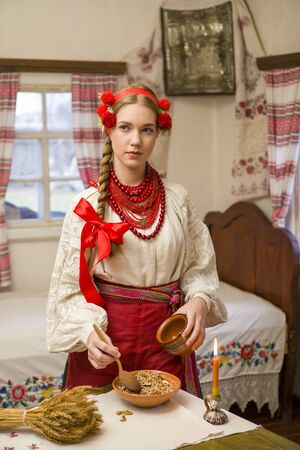 Beautiful girl in national dress is preparing a festive dinner. In a beautiful wreath and a red embroidered dress. Family celebration and celebration of national custom. Bowl with kutia - traditional Christmas sweet meal in Ukraine, Belarus