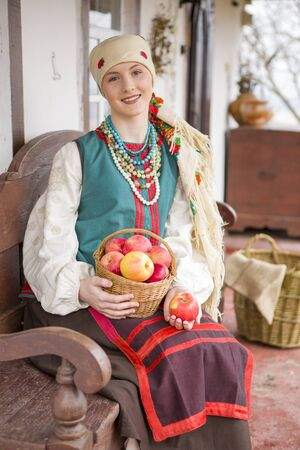 A beautiful girl in national dress is sitting. With apples in a basket. In old clothes of the 19th century. With a wreath and ribbons. Against the background of the ancient city. Village, countryside in the photo