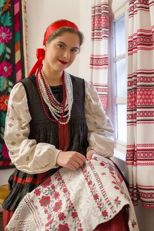 Beautiful young girl in a national costume of the 19th century. Embroiders a beautiful pattern near the window. With a wreath and ribbons. Village, countryside in the photo. In a head scarf.
