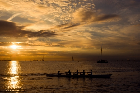 Sports team rowing in a canoe at sunset