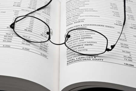 white sheet: Modern thin reading glasses on open business book with balance sheet numbers