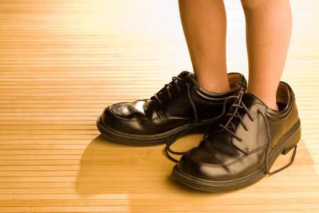 large size: Big shoes to fill, childs feet in large grown-up black shoes, on backlit wood floor, playing dress-up Stock Photo