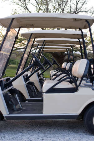 country club: Several golf carts lined up in a row at country club, at sunset Stock Photo
