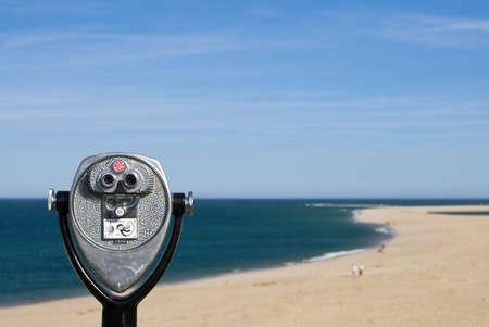 観察: ビーチの観察、青い空と海、砂浜のビーチのための作動させた双眼鏡をコインします。