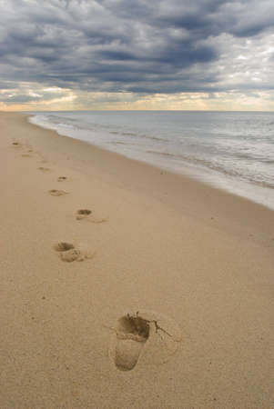 Lonely footprints on a sandy beach, under dark stormy clouds at sunset