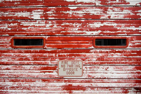 chipped paint: Vintage fire department wooden garage door with peeling, faded red paint