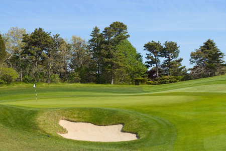 destination scenic: Sand trap and putting green with flag at golf course, country club Stock Photo