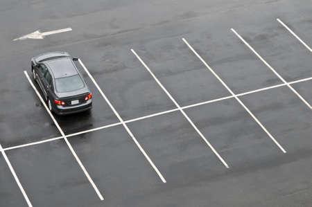Enkele auto in de verder lege parking, in de regen Stockfoto