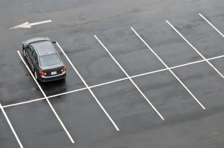 space area: Single car in otherwise empty parking lot, in the rain